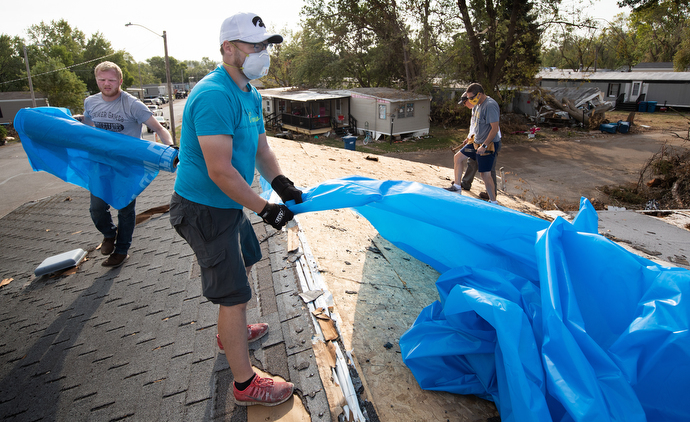 The Rev. Simon Campbell (center foreground) helps spread a plastic tarp over the roof of a storm-damaged home in Marion, Iowa. Campbell was leading a volunteer team from Marion Cares, a ministry of Marion First United Methodist Church. Volunteer Tyler Hungate is at left. Photo by Mike DuBose, UM News.