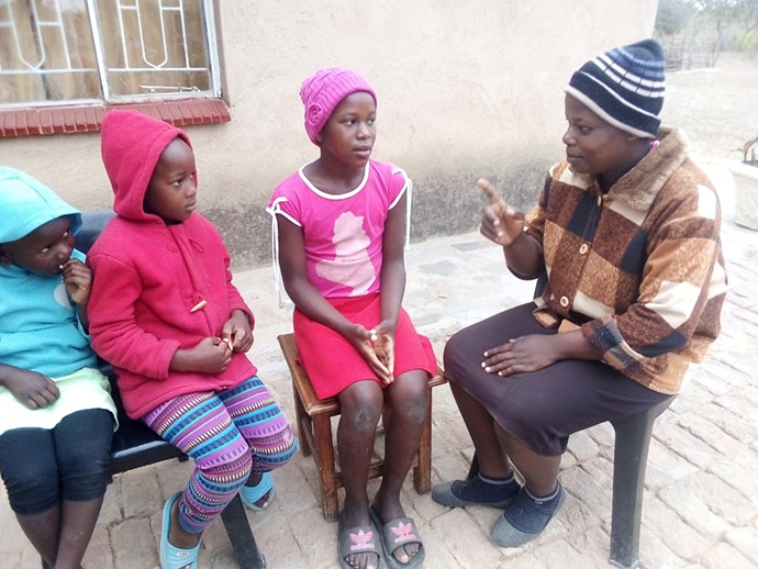 Perpetual Makadzange talks to her three children, (from left) 6-year-old Tizzy, 7-year-old Tanatswa and 12-year-old Tsepang, at their home in the Chimanimani, Zimbabwe. The United Methodist schools that the children attend remain closed to stop the spread of the coronavirus. Photo by Kudzai Chingwe, UM News.