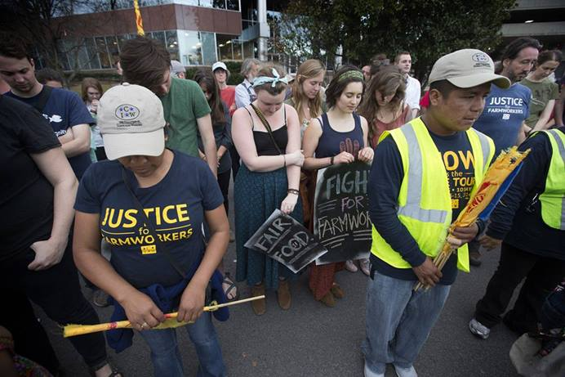 """Membros e apoiadores da Coalition of Immokalee (Fla.) Workers (Aliança dos Trabalhadores de Immokalee, Flórida) oram em Nashville, Tennessee, na conclusão de um protesto contra a recusa da rede de supermercados Publix em aderir a um programa de direitos trabalhistas dos trabalhadores agrícolas. O Livro de Resoluções da Igreja Metodista Unida exige que os empregadores """"tratem os trabalhadores agrícolas e suas famílias com dignidade e respeito"""". Foto de Mike DuBose, Notícias MU."""