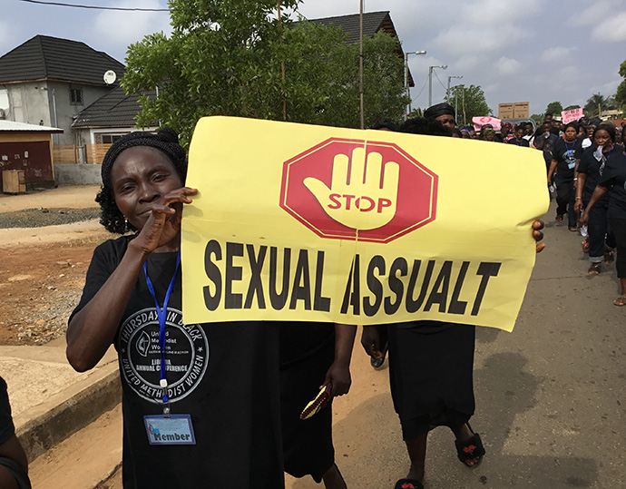 A woman holds a sign calling for an end to sexual violence against women and girls in Liberia. File photo by E Julu Swen, UM News.
