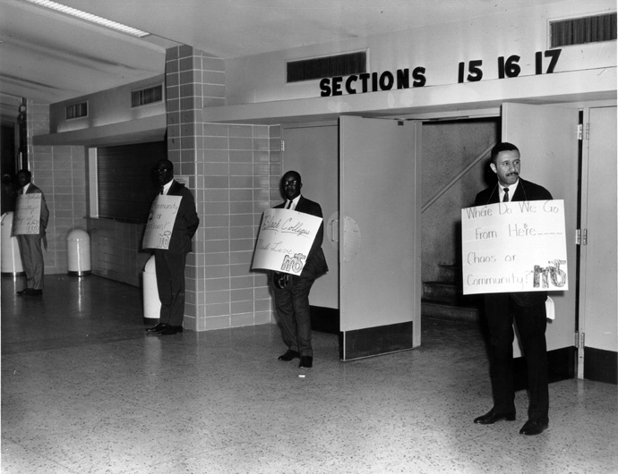 """""""Where do we go from here … Chaos or Community?"""" appears on the sign held by the Rev. Gil Caldwell by the entrance to the 1968 Uniting Conference in Dallas. The gathering officially formed The United Methodist Church and ended the segregated Central Jurisdiction. Caldwell used the title of the Rev. Martin Luther King Jr.'s final book to remind delegates of the church's ongoing call to confront racism. Photo courtesy of Archives and History."""