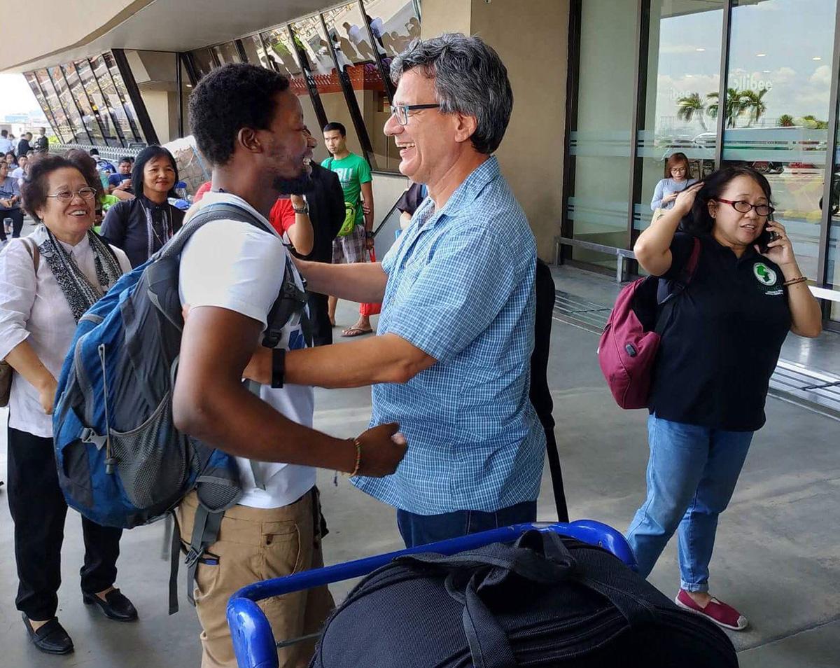 El misionero metodista unido Tawanda Chandiwana, en primer plano a la izquierda, es abrazado por Thomas Kemper, jefe de la Junta de Ministerios Globales, en el Aeropuerto Internacional Ninoy Aquino en Manila, Filipinas, el 1 de julio de 2018, después de que Chandiwana fuera liberado de un centro de detención y se le permitiera para salir del país. Foto de archivo de 2018 cortesía de Thomas Kemper, GBGM.