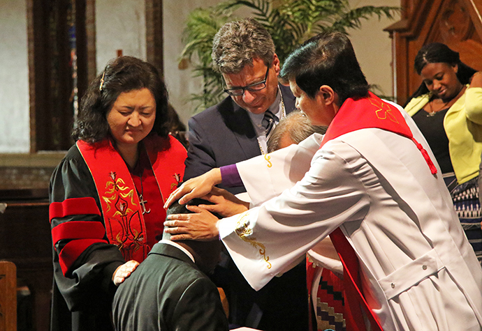 Global Ministries holds the 2017 Global Missionary Commissioning Service in the sanctuary of Grace United Methodist Church in Atlanta. The Rev. Judy Chung, Thomas Kemper, Bishop Hee-Soo Jung and Bishop Pete Torio lay hands on Temba Darlington Nkomozepi, commissioning him into service. File photo by Cynthia Mack, Global Ministries.
