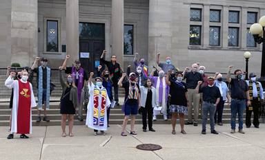 The Rev. Grace Cajiuat (third from left in front row), pastor of Wesley United Methodist Church in Kenosha, Wis., protests with other interfaith religious leaders at Simmons Library Park on Sept. 1, the day President Trump visited the city near Milwaukee. Photo by Chris Herigstad.