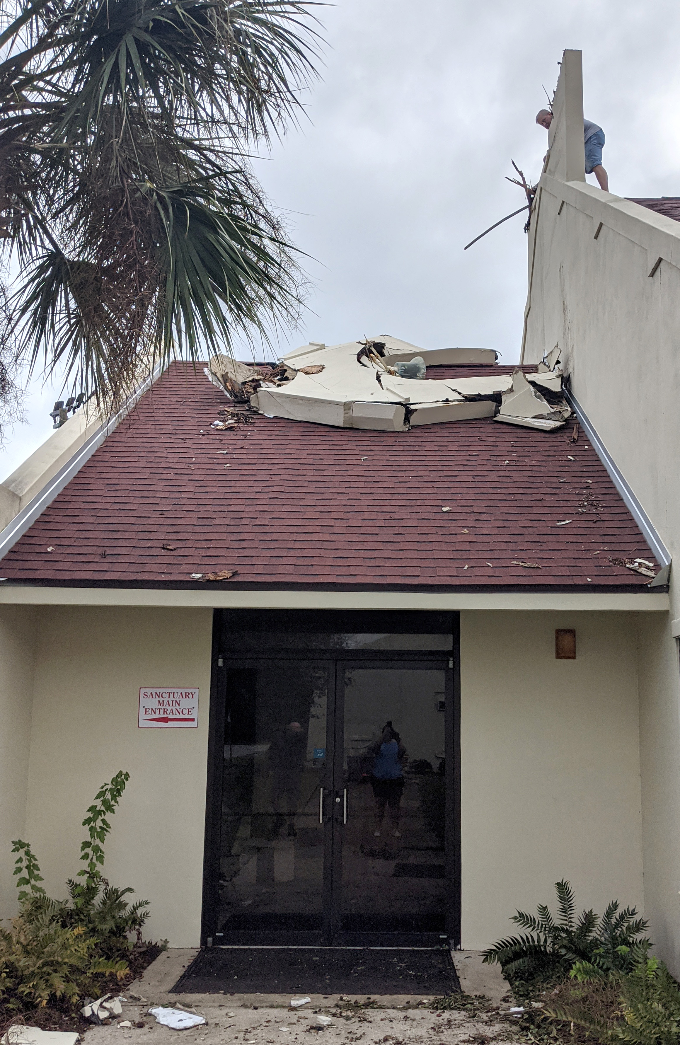 A man on the roof inspects the toppled bell tower at St. Paul United Methodist Church in Gulf Breeze, Fla. Hurricane Sally also caused some water damage to the church.  Photo courtesy of the Rev. Christina Shaver.