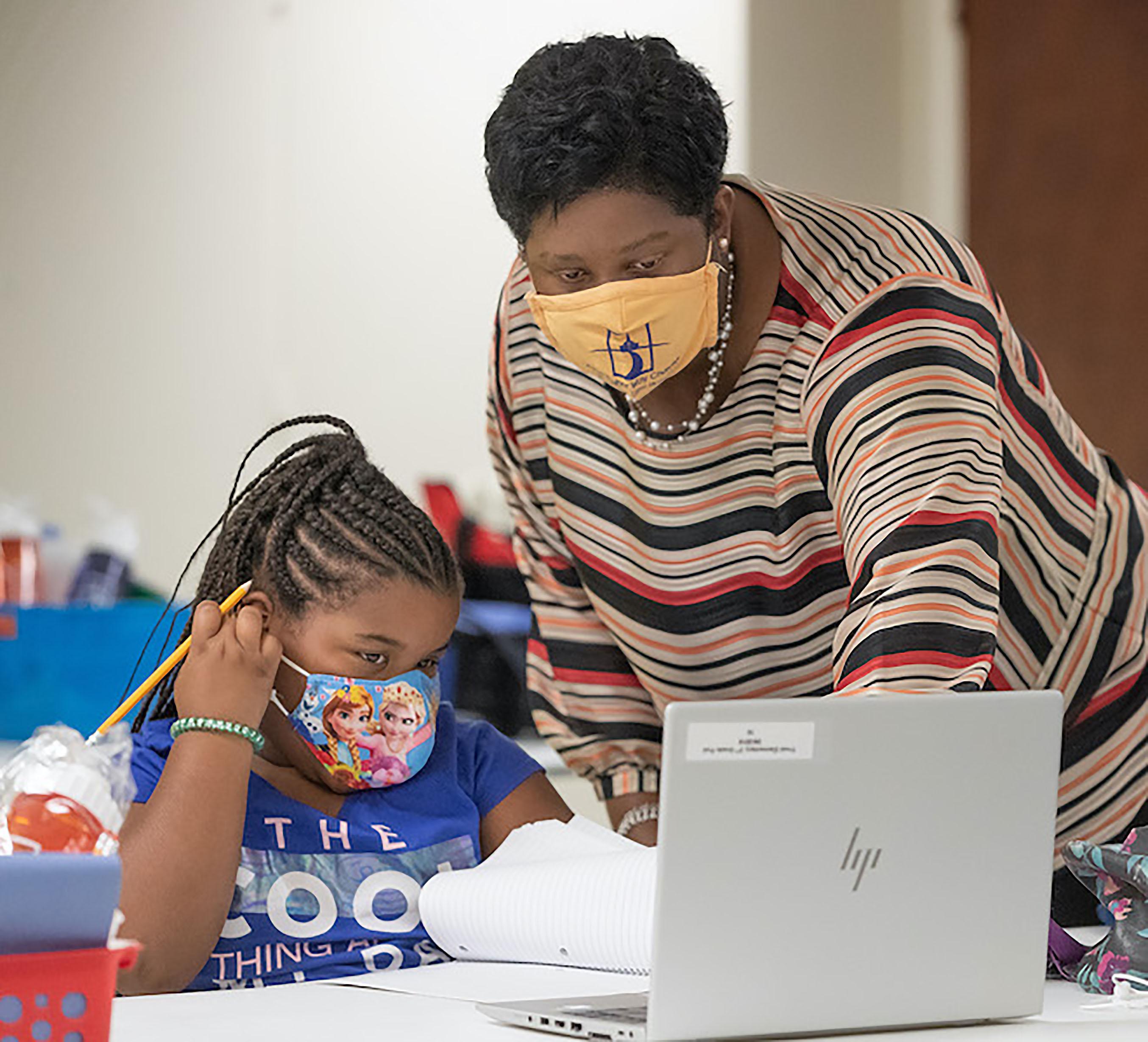 La Revda. Enid Henderson ayuda a una estudiante de primer grado con sus lecciones durante el primer día del programa Santuarios de Aprendizaje en la IMU Jones Memorial en Crestmont Park, Houston. Foto de Mike DuBose, Noticias MU.