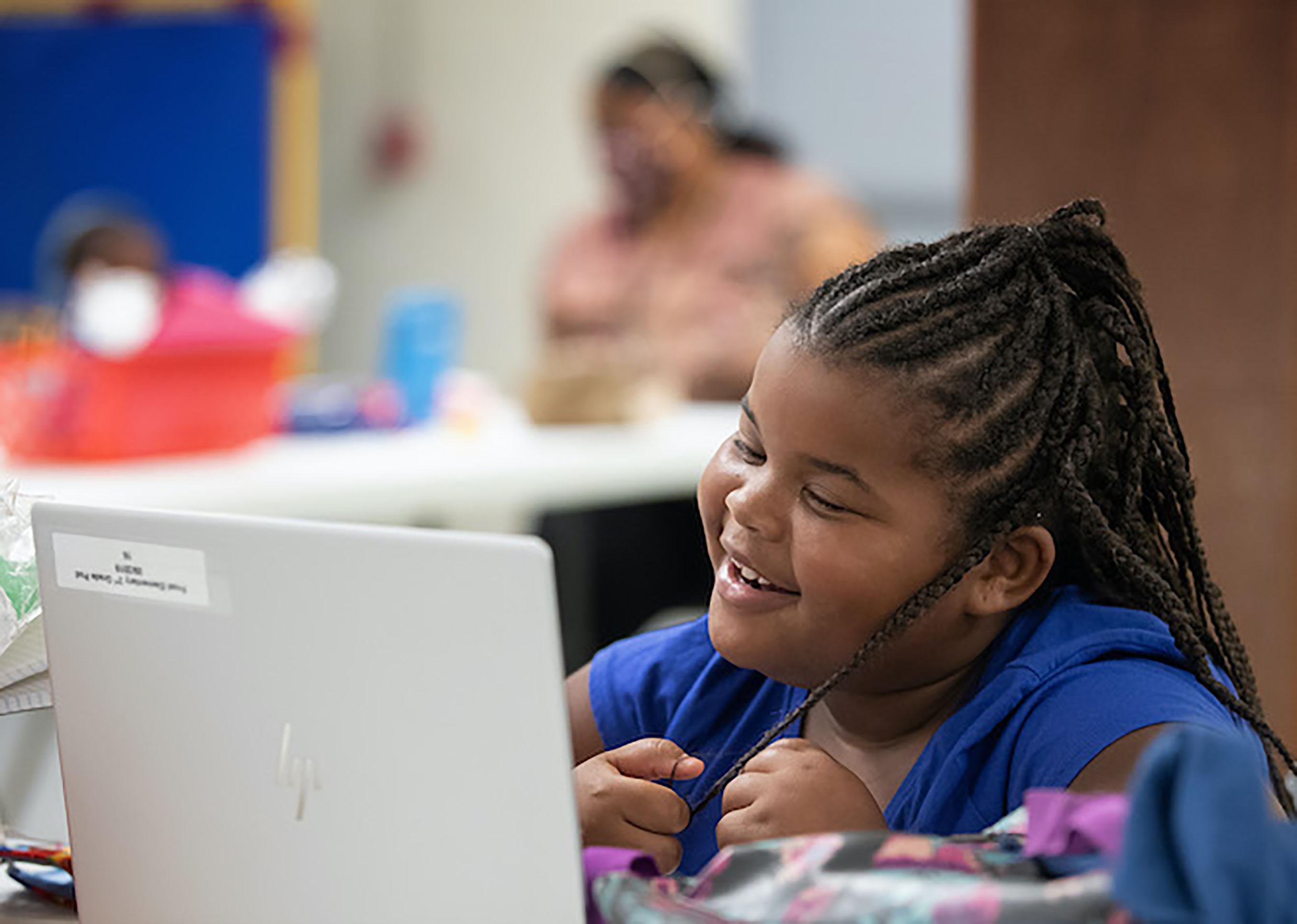 Una estudiante de primer grado interactúa con su maestro y compañeros/as de clase por computadora durante el primer día del programa Santuarios de Aprendizaje en la IMU Jones Memorial en Crestmont Park, Houston. Foto de Mike DuBose, Noticias MU.