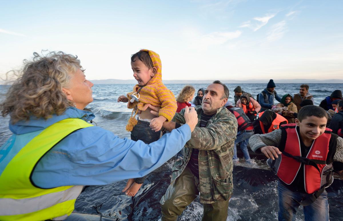 Voluntarios/as llevan a un niño a tierra en una playa cerca de Molyvos, en la isla griega de Lesbos, el 30 de octubre de 2015, después de que un grupo de refugiados/as cruzara el mar Egeo desde Turquía en un pequeño bote abarrotado de gente, proporcionado por traficantes turcos a quienes les habían pagado enormes sumas de dinero. Los/as refugiados/as fueron recibidos/as en Grecia por voluntarios/as locales e internacionales y luego se dirigieron hacia Europa occidental. Foto de archivo de Paul Jeffrey / Life on Earth Pictures.