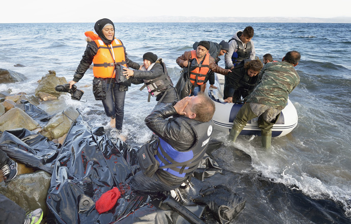When he landed on the Greek island of Lesbos on Oct. 30, 2015, Nabil Minas, a Christian refugee from Syria, carried his children through the water and left them on the shore, then fell on his face and kissed the ground. The shore where he kneels is covered with the black rubber of deflated refugee boats. Minas and his family came in the boat from Turkey, paying an exorbitant amount to traffickers who provided the transport. File photo by Paul Jeffrey/Life on Earth Pictures.