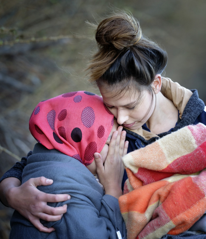 A volunteer embraces a sobbing refugee woman who just landed on a beach near Molyvos, on the Greek island of Lesbos, on Oct. 31, 2015, after crossing the Aegean Sea from Turkey. File photo by Paul Jeffrey/Life on Earth Pictures.