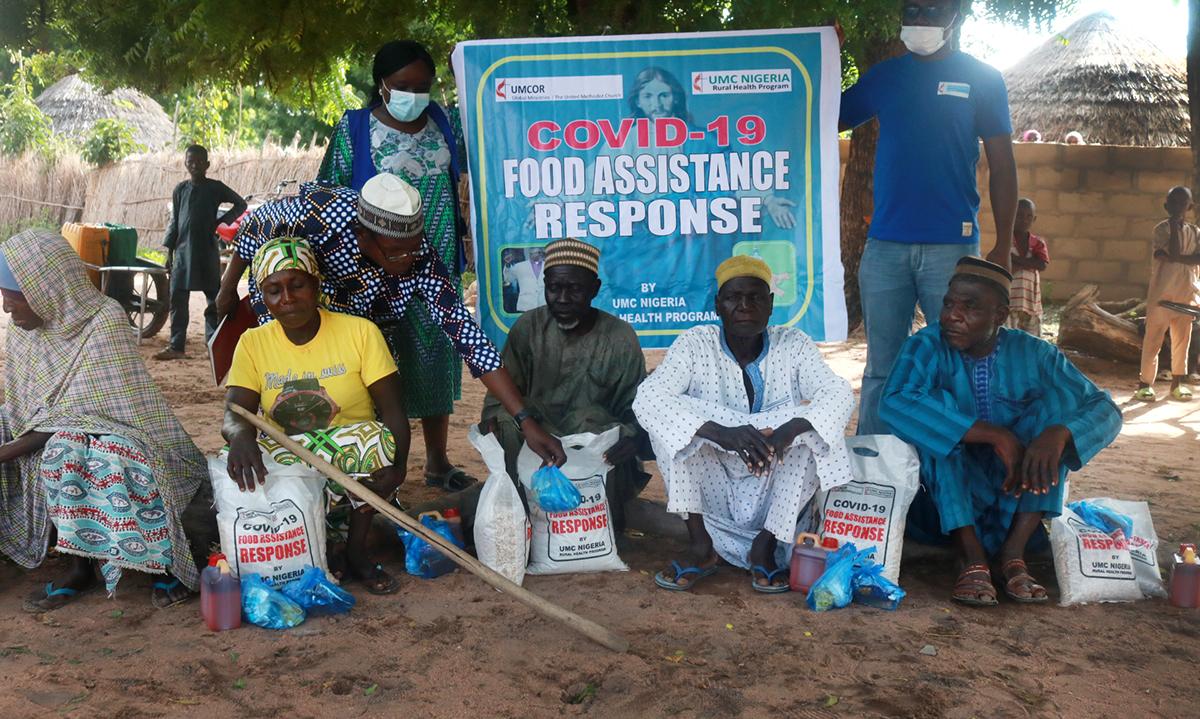 Les bénéficiaires de Mutum-Daya, dans le district central de Wurkun au Nigeria, reçoivent du riz, des haricots, de l'assaisonnement Maggi et du sel dans le cadre de l'action liée à la COVID-19 de l'Église méthodiste unie. La Région épiscopale du Nigeria a reçu une subvention « Sheltering in Love » du Fonds de réponse COVID-19 de UMCOR. Photo de Richard Fidelis, UM News.