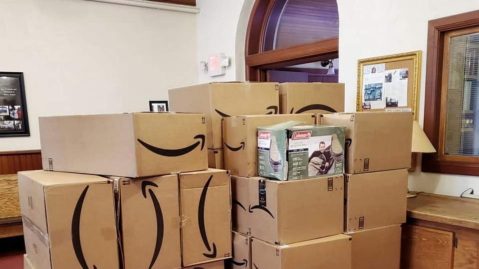 Pilhas de caixas com sacos de dormir doados para os desabrigados ocupam espaço no andar de baixo da Igreja Aspen Community. Foto de cortesia Aspen Community United Methodist Church.