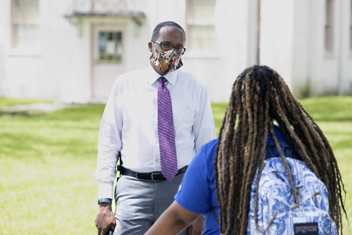 Walter Kimbrough, president of Dillard University in New Orleans, talks with a student on campus. Kimbrough is participating in a COVID-19 vaccine study at Ochsner Medical Center in New Orleans. Photo by Sabree Hill, Dillard University.