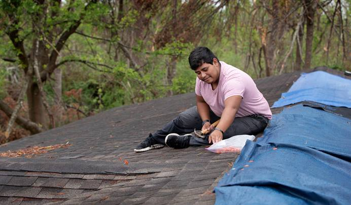 Caton Darling, 17, secures a tarp over the roof of his family's home in Lake Charles, La., after Hurricane Laura toppled trees that damaged the roof.