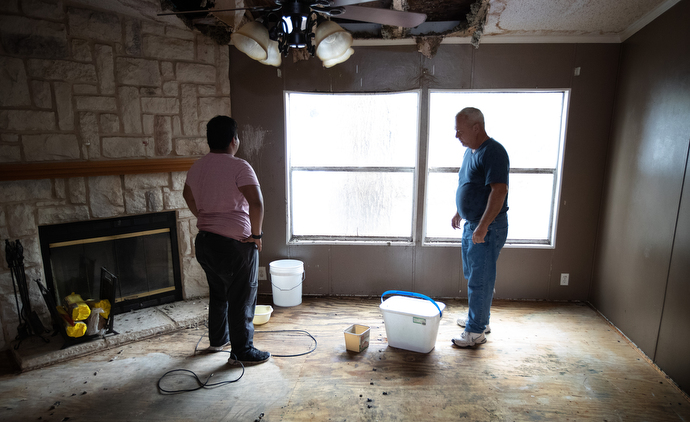 Caton Darling (left) and his father, Eric, arrange containers to catch drips of rainwater at their home in Lake Charles, La., which was damaged by Hurricane Laura. Photo by Mike DuBose, UM News.