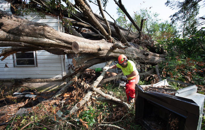 Volunteer John Meier works to remove a fallen tree from a home in DeRidder, La., following Hurricane Laura. Meier is a member of the Early Response Team of the Louisiana Conference of The United Methodist Church. Photo by Mike DuBose, UM News.