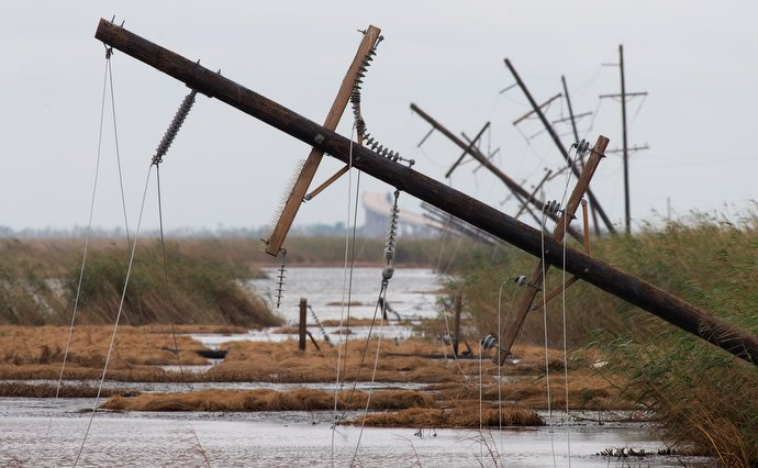 Power poles toppled by Hurricane Laura lie alongside the West Creole Highway near Cameron, La. The Category 4 storm left thousands without power. The Conway LeBleu Memorial Bridge over the Intracoastal Waterway is visible in the background. Photo by Mike DuBose, UM News.