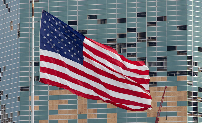 A United States flag flies in front of the Capital One Tower in Lake Charles, La., following Hurricane Laura. The storm shattered many windows in the office building, some of which have been boarded up with plywood. Photo by Mike DuBose, UM News.