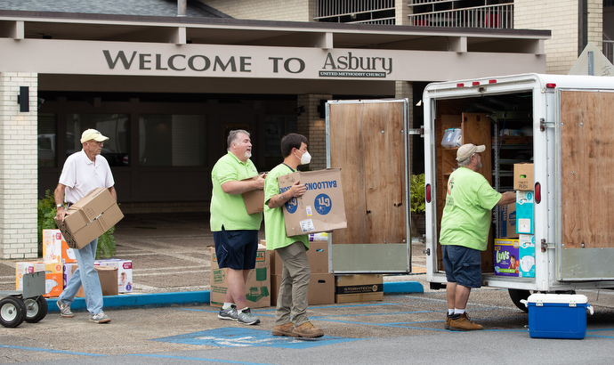 Volunteer Lou Groth (left) helps a United Methodist volunteer team from North Carolina load relief supplies for survivors of Hurricane Laura at Asbury United Methodist Church in Lafayette, La. Photo by Mike DuBose, UM News.