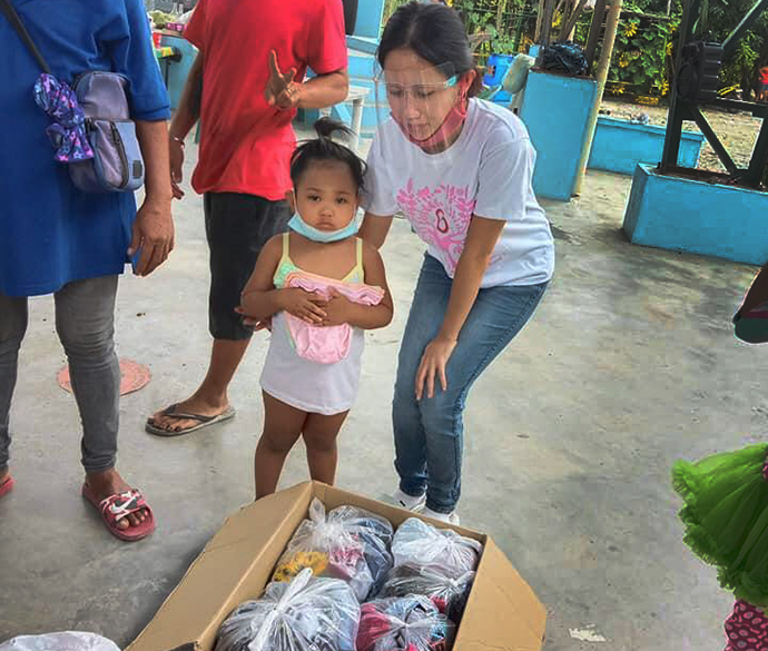 Jazel Resurreccion Lustre, a volunteer teacher in Bulacan province, helps a child from the Longos neighborhood, which was devastated by fire. The September blaze destroyed 28 of 108 homes in the impoverished community. Photo by Emily Sison.
