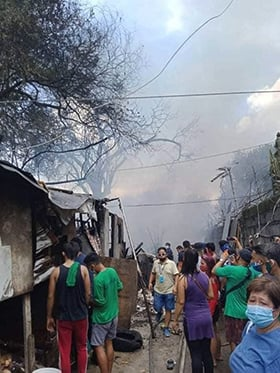 Residents of the Longos barangay, or neighborhood, watch as smoke billows over their neighborhood. A September fire destroyed 28 of 108 homes in the impoverished community in Bulacan province. Photo courtesy of Fort Nicolas.