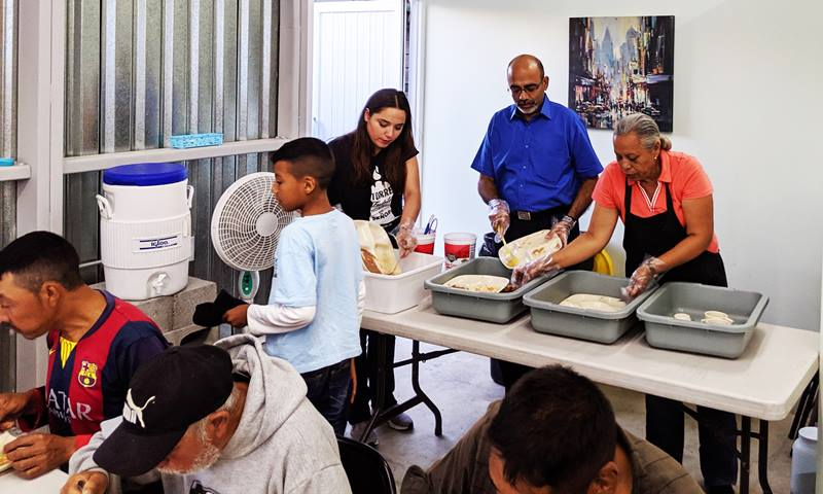 Roland Fernandes (al centro en la fila de atrás) trabaja con voluntarios/as mexicanos/as y estadounidenses en el Comedor Juan 6: 35, una cocina en Tijuana que proporciona comidas a los/as migrantes que llegan. Foto de Mia Nieves.