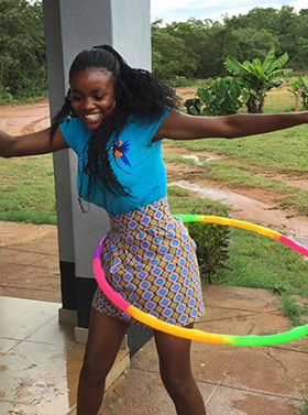Nineteen-year-old Winnet Mandikisi, an orphan who spent her teenage years at The United Methodist Church's Home of Hope, has fun with a hula hoop at Nyadire Mission in Mutoko, Zimbabwe. Mandikisi has been teaching orphans at the home how to make masks and sanitary pads while schools have been closed during the coronavirus pandemic. Photo by Chenayi Kumuterera, UM News.