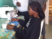 Winnet Mandikisi, 19, works at a sewing machine at Home of Hope, the orphanage at Nyadire United Methodist Mission in Mutoko, Zimbabwe. Mandikisi, a college student, has been leading efforts to teach fellow orphans how to make masks to fight against COVID-19. Photo by Chenayi Kumuterera, UM News.