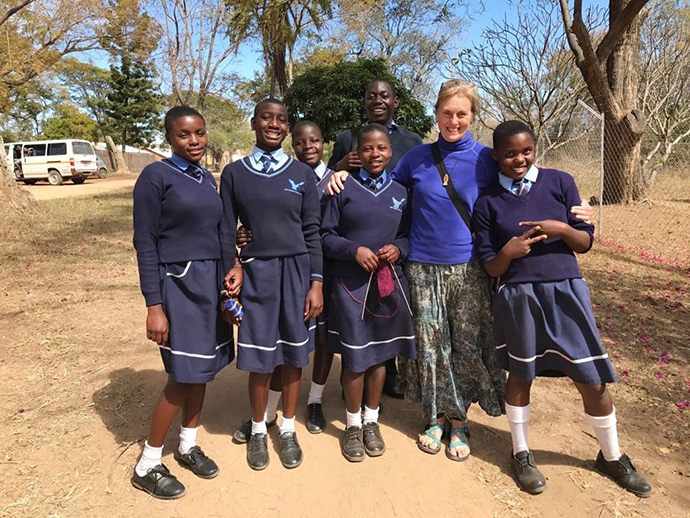 Mary Beth Zollars (second from right) with the Nyadire Connection stands with students, including Winnet Mandikisi (left), at The United Methodist Church's Home of Hope orphanage. Photo by Chenayi Kumuterera, UM News.