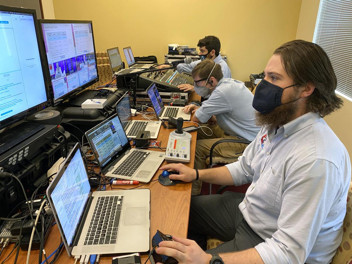 Uma visão da sala de controle de vídeo do GNTV Media Ministry durante a reunião anual da Conferência Baltimore-Washington mostra várias telas de computador, equipamento de áudio e técnicos ocupados. Foto cortesia do GNTV Media Ministry.