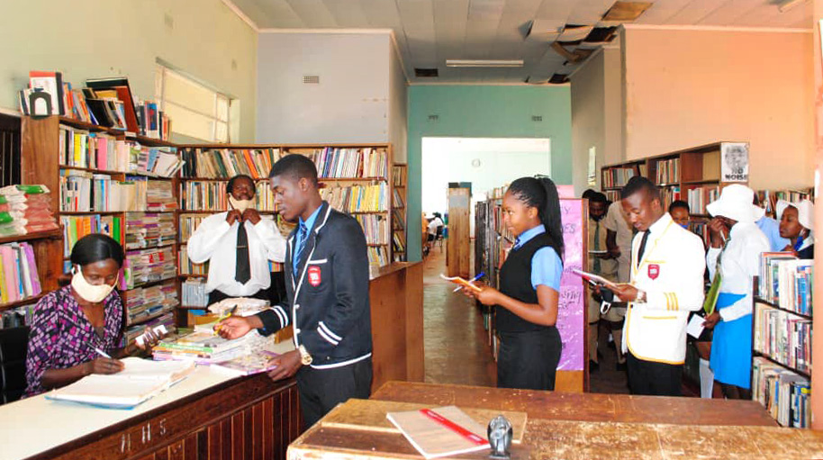 Rachel Barwe issues textbooks to students in the library at Hartzell High School, a United Methodist school at Old Mutare Mission in Mutare, Zimbabwe. A 2019 fire burned many of the school's textbooks, creating challenges for students and staff. Photo by Kudzai Chingwe, UM News.