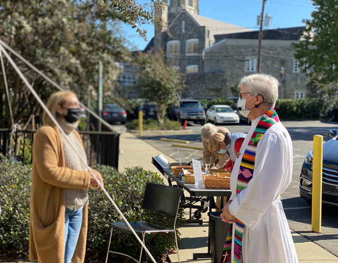 The Rev. James Howell, senior pastor at Myers Park United Methodist Church in Charlotte, N.C., greets a member outside the church where a communion service was held with social distancing. Photo by Sarah Gibson.