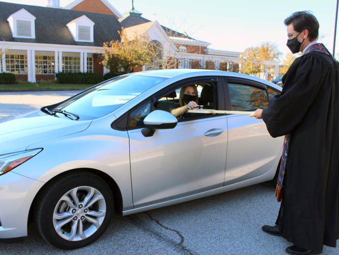 The Rev. Andy Bryan uses an oar to deliver communion elements safely for an Election Day drive-thru communion service at Manchester United Methodist Church in Manchester, Missouri. Photo by Phil Wiseman.
