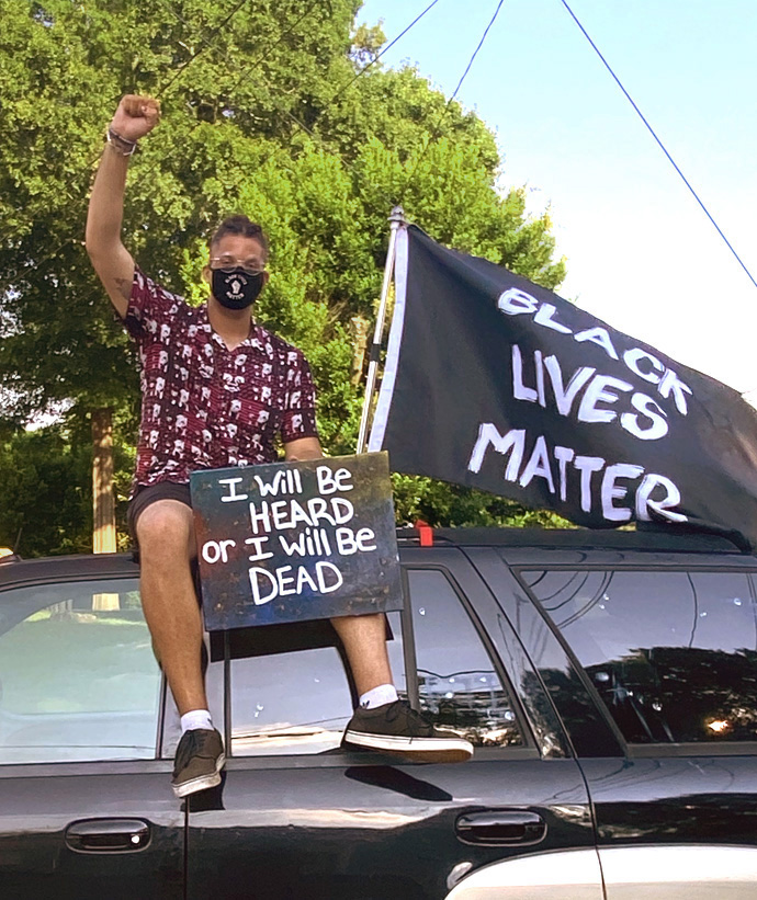 Derian Wilson who protests racism regularly in Macon, Ga., sits atop an SUV during a demonstration. Photo courtesy of Derian Wilson.