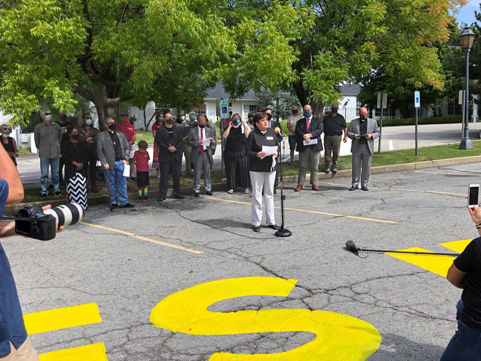 "The Rev. Kathy Brown, pastor of St. Paul's United Methodist Church in Tulsa, Okla., speaks at the church, which has painted ""Black Lives Matter"" on its parking lot. Photo courtesy of the Rev. Twila Gibbens."