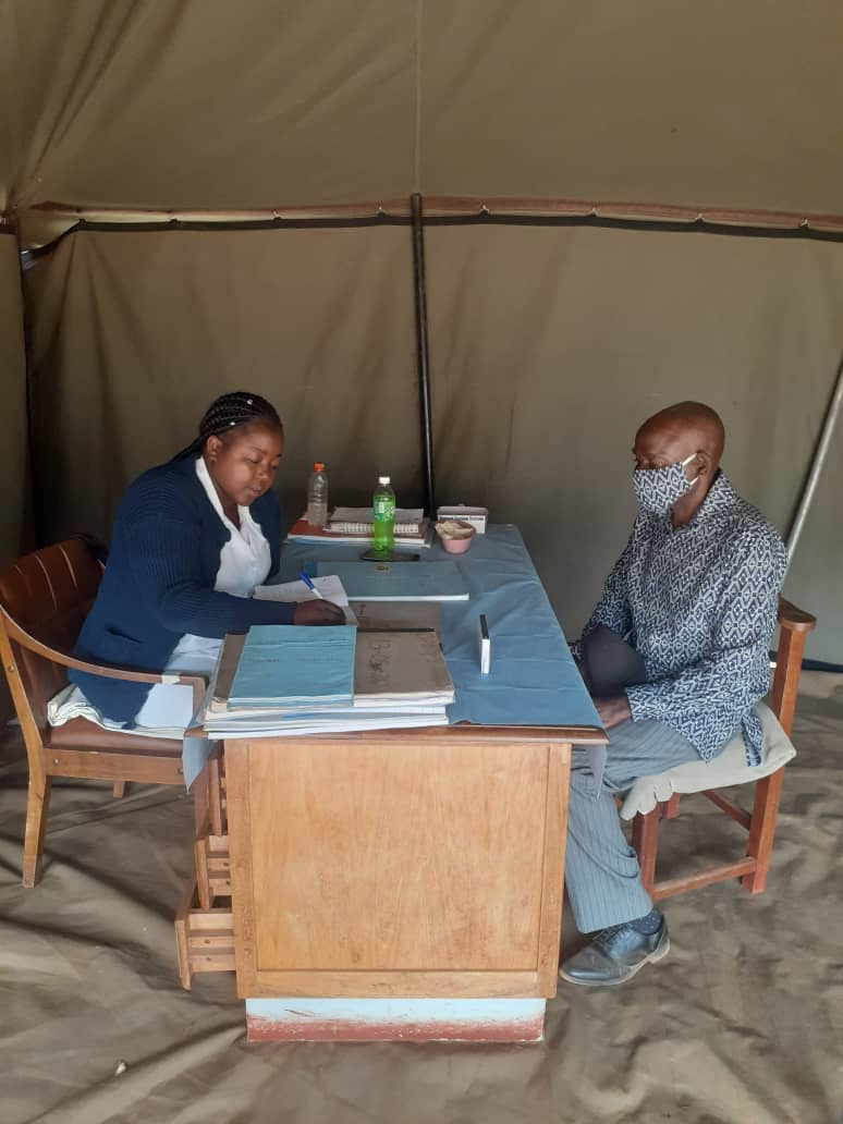 Portia Gogode attends to patient Steven Nyakudarika, 73, inside a tent set up outside Old Mutare Mission Hospital in Mutare, Zimbabwe. Tents are being used to protect patients and staff during the pandemic. Photo by Kudzai Chingwe, UM News.