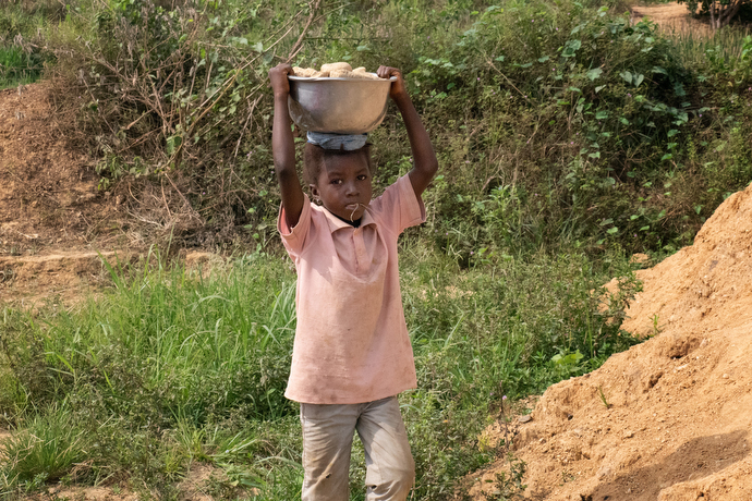 Kaday Kargbo, 5, carries a load of rocks to his family's roadside stand in Kono. The family breaks down the larger rocks from an artisanal diamond mining operation to sell to people who need them for their yards or gardens. Photo by Kathy L. Gilbert, UM News.
