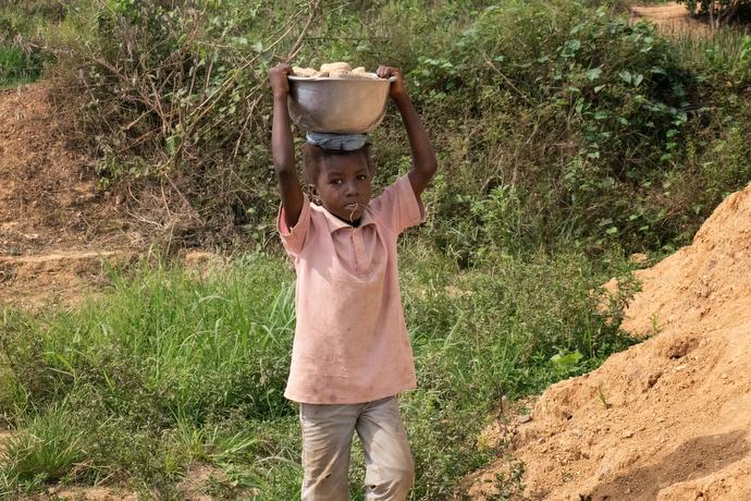 Kaday Kargbo, 5 ans, transporte un chargement de pierres au stand de sa famille situé sur le bord de la route à Kono. La famille brise les plus grosses pierres provenant d'une exploitation minière artisanale de diamants pour les vendre aux personnes qui en ont besoin pour leurs cours ou leurs jardins. Photo de Kathy L. Gilbert, UM News.