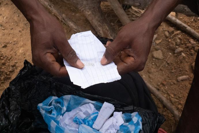 Le propriétaire d'une mine de diamants artisanale à Kono déballe un petit paquet de diamants. Il emploie des personnes locales pour travailler dans son exploitation. Photo de Kathy L. Gilbert, UM News.