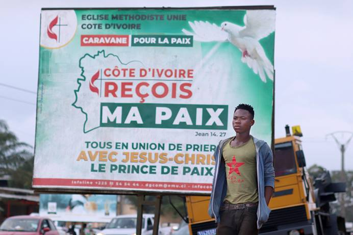 A pedestrian passes one of The United Methodist Church's billboards calling for peace in the community of Abobo, Côte d'Ivoire. The United Methodist Church and its partners organized a communication campaign asking that the population and the authorities show restraint during the electoral period. The caravan crisscrossed several towns and hamlets in Côte d'Ivoire. Photo by Isaac Broune, UM News.