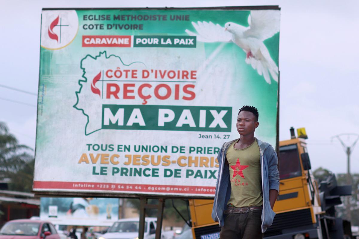 Un piéton passe devant l'un des panneaux publicitaires de l'Église Méthodiste Unie appelant à la paix dans la commune d'Abobo, en Côte d'Ivoire. L'Église Méthodiste Unie et ses partenaires ont organisé une campagne de communication demandant à la population et aux autorités de faire preuve de retenue pendant la période électorale. La caravane a traversé plusieurs villes et hameaux de Côte d'Ivoire. Photo d'Isaac Broune, UM News.