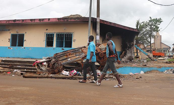 Les restes d'un véhicule incendié devant le commissariat de police criblé de balles près de l'église Méthodiste Unie Emmanuel (à droite, au fond) de Bonoua, à 50 kilomètres au sud-est d'Abidjan, en Côte d'Ivoire. Le 13 août 2020, des manifestants ont mis le feu au bâtiment pour protester contre la décision du président Alassane Ouattara de se présenter pour un troisième mandat contre la constitution. Selon les autorités locales, un garçon de 18 ans a été tué par les forces de l'ordre. Photo d'Isaac Broune, UM News.