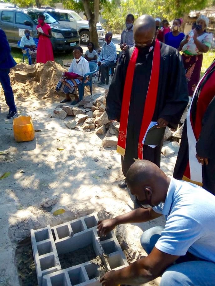 O Construtor preparando o terreno para lançamento da pedra em Dondo, Moçambique. No fundo vê-se os membros daquela comunidade sentados. Foto de Eurico Gustavo.