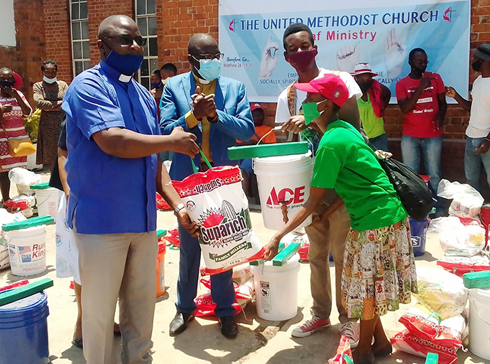 The Rev. Chrispen Musuruware (left) of Hilltop United Methodist Church in Mutare, Zimbabwe, helps distribute food and other supplies to Deaf church members in October, 2020. The distribution was funded by a $5,000 Sheltering in Love grant from the United Methodist Committee on Relief. Photo courtesy of Hilltop United Methodist Church Communications.