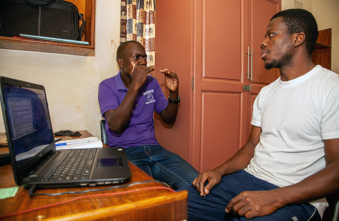 Tonderai Makaya (left) helps interpret an online class for Collins Prempeh, a Deaf theology student at Africa University in Zimbabwe. Prempeh, 36, is from Ghana. Both men are members of Hilltop United Methodist Church in Mutare, Zimbabwe. Photo courtesy of Africa University.
