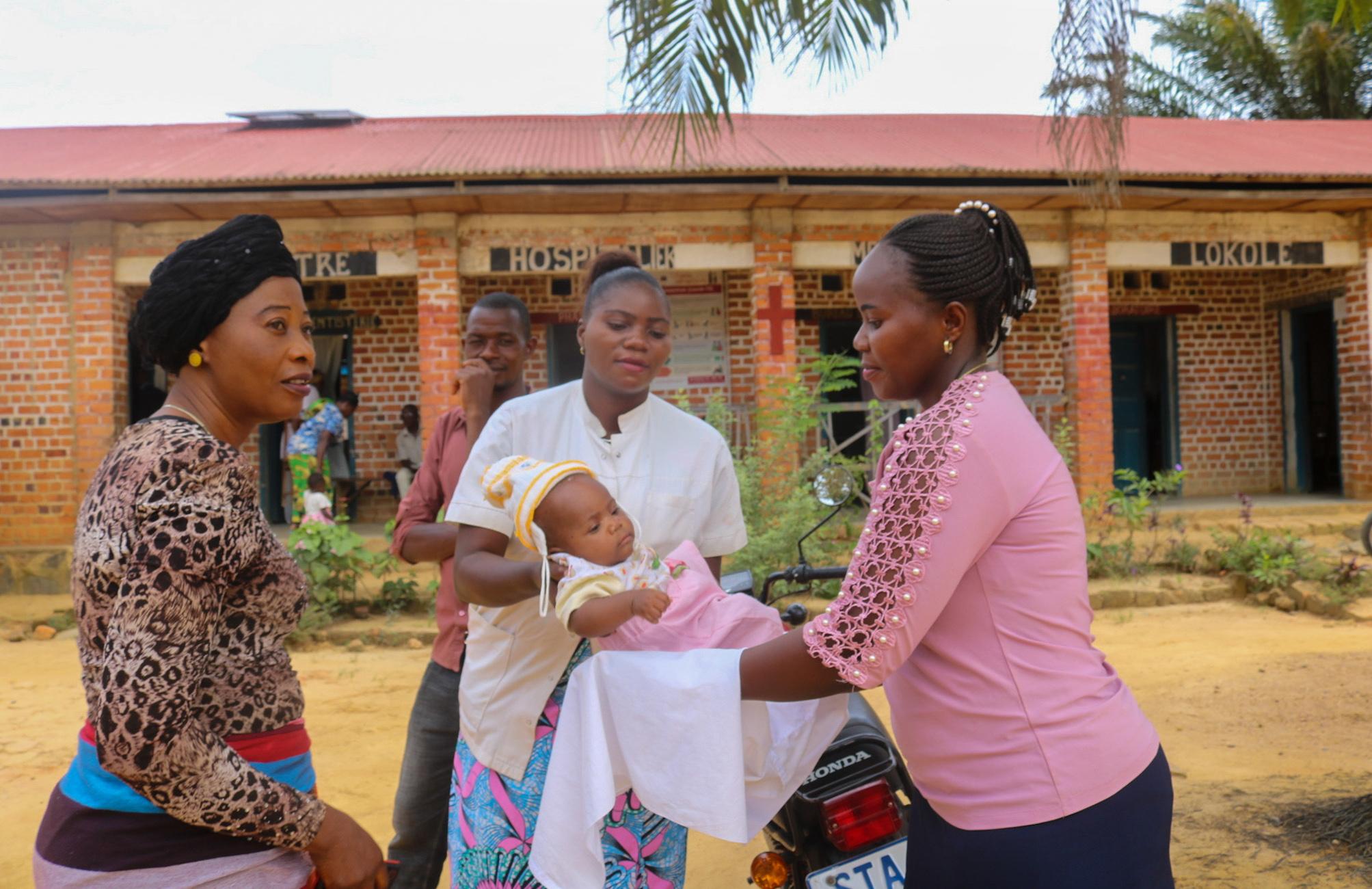 Une infirmière de l'Hôpital Méthodiste Uni de Lokolé à Kindu, en RDC, rend un enfant à sa mère après une séance de vaccination de routine. Les hôpitaux et cliniques de l'Église Méthodiste Unie contribuent à la vaccination de milliers d'enfants chaque année dans le pays. Photo de Chadrack Tambwe Londe, UM News.