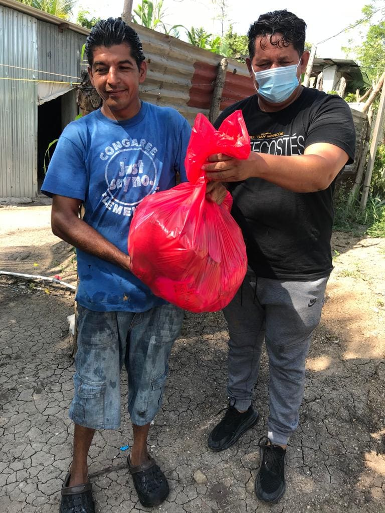 El Pastor Félix Medina (derecha), junto con voluntarios/as de la IMU Casa de Paz reparten alimentos, donados por miembros de la comunidad, entre familias que han sido afectadas en las áreas vecina a la iglesia. Foto cortesía de la IMU Casa de Paz.