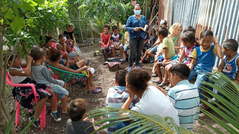 Voluntarios/s de la IMU Casa de Paz en Villanueva, Honduras, atienden a niños/as en el refugio de la iglesia, donde conviven 40 familias de las cuales 8 son miembros de esta congregacion metodista. El Pastor Félix Medina (derecha), junto con voluntarios/as de la IMU Casa de Paz reparten alimentos, donados por miembros de la comunidad, entre familias que han sido afectadas en las áreas vecina a la iglesia. Foto cortesía de la IMU Casa de Paz.