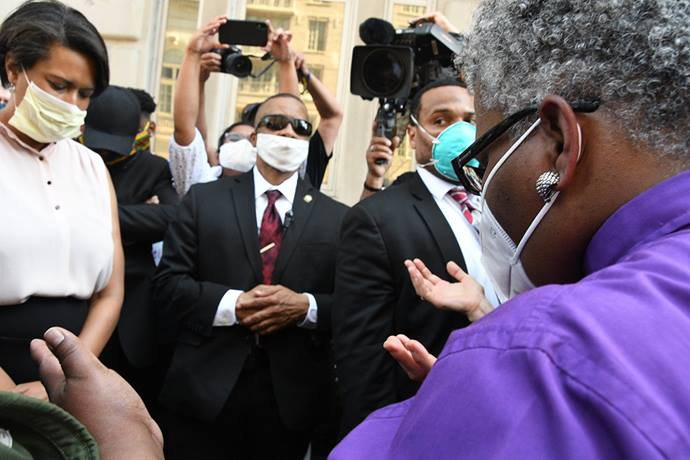 United Methodist Bishop LaTrelle Easterling (right) offers a prayer during an interfaith vigil near the White House on June 3. At left is Washington Mayor Muriel Bowser. United Methodist conferences are confronting the sin of racism through prayers, calls for justice and education on white supremacy. File photo by Melissa Lauber, Baltimore-Washington Conference.