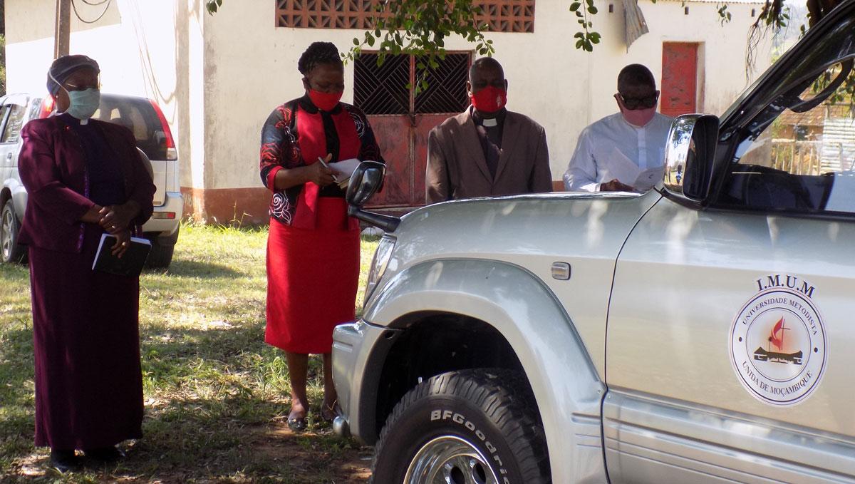 Bispa Joaquina Filipe Nhanala (a primeira de esquerda para a direita) orando durante a cerimónia da dedicação da viatura para a Universidade Metodista Unida de Moçambique no Cambine, Moçambique. Foto de António Wilson.